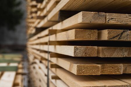 Piles of wooden boards in the sawmill, planking. Warehouse for sawing boards on a sawmill outdoors. Wood timber stack of wooden blanks construction material. Industry