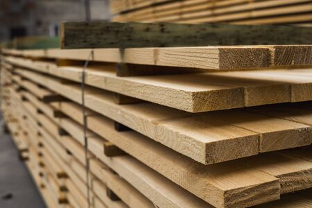 Piles of wooden boards in the sawmill, planking. Warehouse for sawing boards on a sawmill outdoors. Wood timber stack of wooden blanks construction material. Industry. Banque d'images