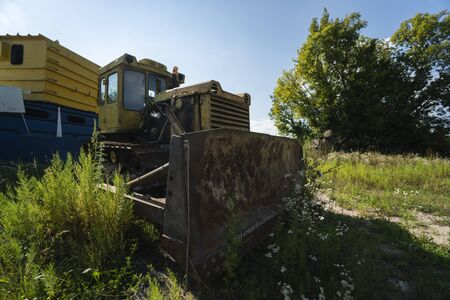 Old yellow rusty tractor in field in sunny day Banque d'images - 137876506