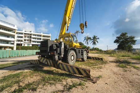 Yellow automobile crane with risen telescopic boom outdoors. Mobile construction crane on a constructin site. Crane machine stand by waiting for work under the construction building. Heavy industry. 版權商用圖片