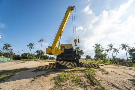 Yellow automobile crane with risen telescopic boom outdoors. Mobile construction crane on a constructin site. Crane machine stand by waiting for work under the construction building. Heavy industry. Stock Photo