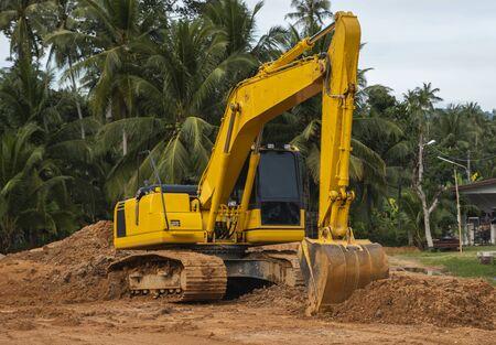 Escavatore giallo in un cantiere edile contro il cielo blu. Industria pesante. Chiudere i dettagli dell'escavatore industriale. Grande escavatore cingolato in piedi su un terreno arancione con palme sullo sfondo Archivio Fotografico