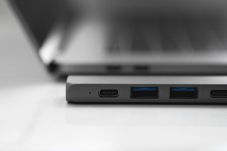 The USB adapter under the Type-C connector for laptop. Multiport station for laptop with multiple different ports. USB to USB Type-C Hub Converter. Gadgets for use a modern laptop