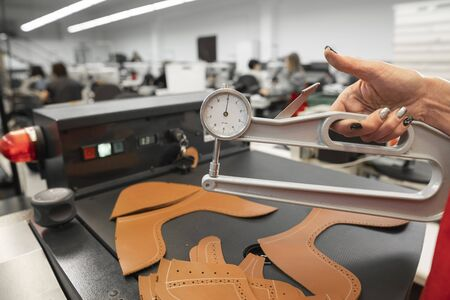 Woman hands use Leather thickness gauge on with a natural brown leather. Preparing of the raw materials for manufacture of bags, shoes, clothing and accessories