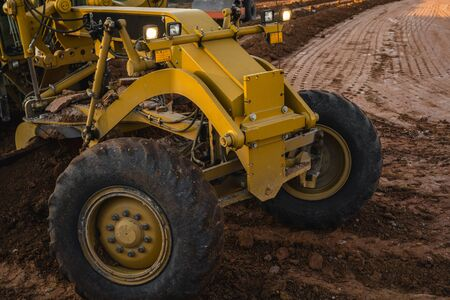 Grader is working on road construction. Grader industrial machine on construction of new roads. Heavy duty machinery working on highway. Construction equipment. Compaction of the road.