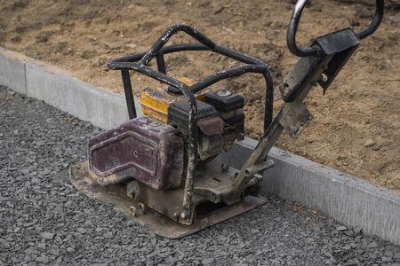 Vibrational paving stone machine for finish on a sidewalk road construction site.