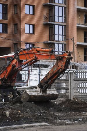 Orange excavator works on construction site with a gravel and carry it fromone place to another. Heavy industry. Construction of a building. Stok Fotoğraf