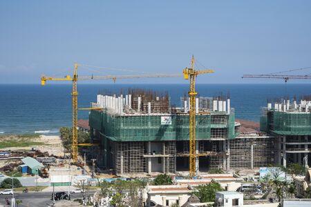 VIETNAM, DA NANG - April 10, 2019: Cranes and building construction site against blue sky and sea. Metal construction of unfinished building on construction. 新聞圖片
