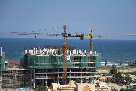 VIETNAM, DA NANG - April 10, 2019: Cranes and building construction site against blue sky and sea. Metal construction of unfinished building on construction. Tower Crane use for building of multi storage building.