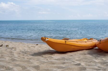 Two colorful orange kayaks on a sandy beach ready for paddlers in sunny day. Several orange recreational boats on the sand. Active tourism and water recreation. 版權商用圖片