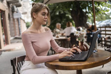 Beautiful young woman in white t-shirt is working on laptop and smiling while sitting outdoors in cafe. Young female using laptop for work. Female freelancer working on laptop in an outdoor cafe. 版權商用圖片
