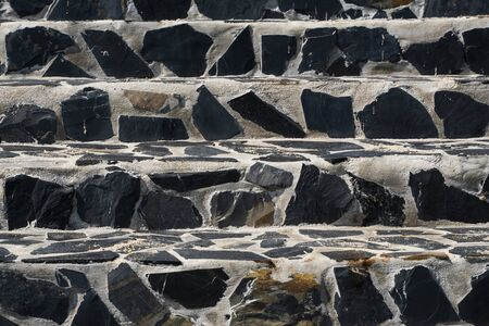 Steintreppe auf der Straße aus schwarzen Steinen und grauem Zement