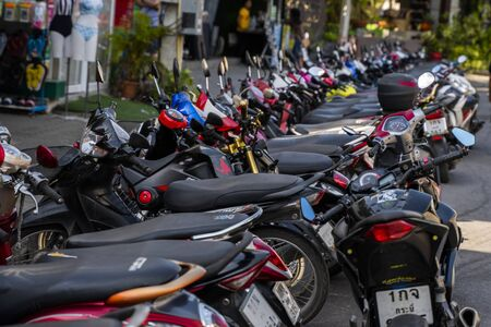 KRABI, THAILAND - JULY 10, 2019. Usual crowded parking place in Krabi with full of motorbikes. A lot of motorcycles parking in rows at sidewalk in tourustic place. 新聞圖片