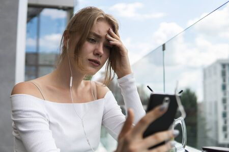 Upset young student watching broadcasting online on modern mobile phone. Blond woman blogger with cocktail is reading incoming sms message on smartphone connected to free wifi in cafe. 版權商用圖片