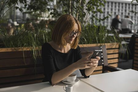 Young business woman uses phone. Good looking brunette female uses online banking on smart phone to transfer money from credit card. Girl using smart phone and chatting with business partners