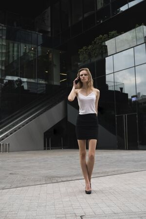 Business woman is talking on the phone with a business partners with a huge windows of a big building on background. 版權商用圖片