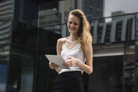 Portrait of smiling business woman holding a tablet computer. Business woman on a meeting and waiting business partner and holding a tablet in hands.
