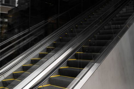 Empty escalators stairway with a yellow stripes