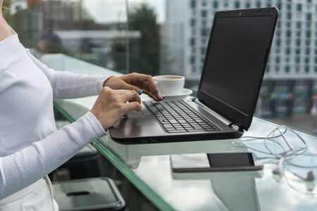 A woman is working by using a laptop computer on table. Hands typing on a keyboard. Female businessman is typing on a laptop keyboard sitting in cafe.