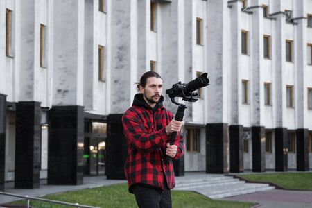Young Professional videographer holding professional camera on 3-axis gimbal stabilizer. Pro equipment helps to make high quality video without shaking. Cameraman wearing red shirt making a videos. 版權商用圖片
