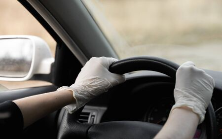 Woman in protective suit, medical mask and rubber gloves for protect from bacteria and virus is driving a car. Protective mask while quarantine, world pandemic, covid 19, coronavirus, infection.