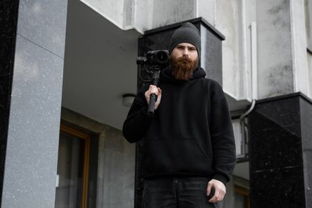 Bearded Professional videographer in black hoodie holding professional camera on 3-axis gimbal stabilizer. Filmmaker making a great video with a professional cinema camera. Cinematographer. 版權商用圖片