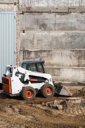 White skid steer loader at a construction site working with a soil. Industrial machinery. Industry.