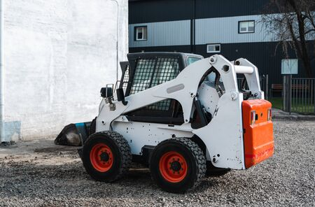 White skid steer loader at a construction site waiting of work. Industrial machinery. Industry Imagens