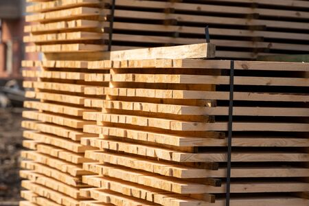 Warehouse for sawing boards on a sawmill outdoors. Timber mill, sawmill. Storage of planed wooden boards. Piles of wooden boards in the sawmill. Planking. Industry. Stok Fotoğraf