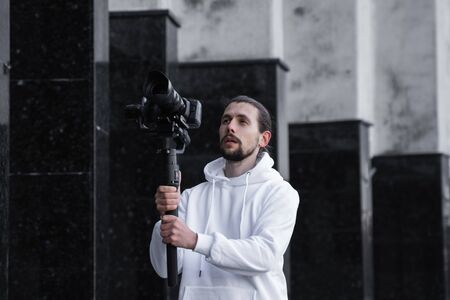 Young Professional videographer holding professional camera on 3-axis gimbal stabilizer. Pro equipment helps to make high quality video without shaking. Cameraman wearing white hoodie making a videos.