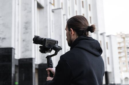 Young Professional videographer holding professional camera on 3-axis gimbal stabilizer. Pro equipment helps to make high quality video without shaking. Cameraman wearing black hoodie making a videos
