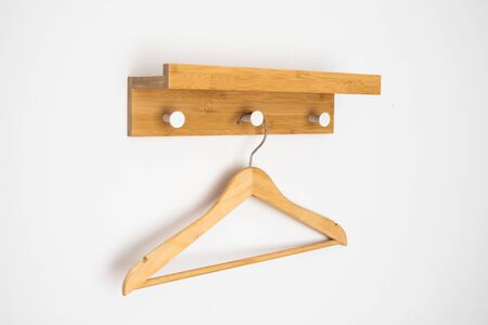 Clothes wooden hanger on a white wall