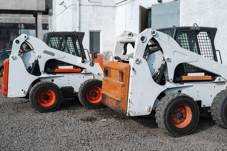 Two white skid steer loader at a construction site waiting of work. Industrial machinery. Industry