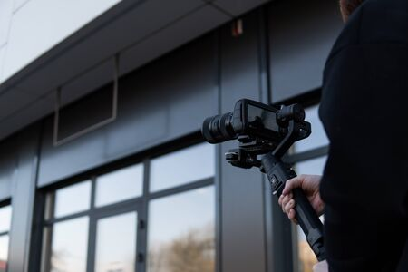 Professional videographer in black hoodie holding professional camera on 3-axis gimbal stabilizer. Filmmaker making a great video with a professional cinema camera. Cinematographer 版權商用圖片