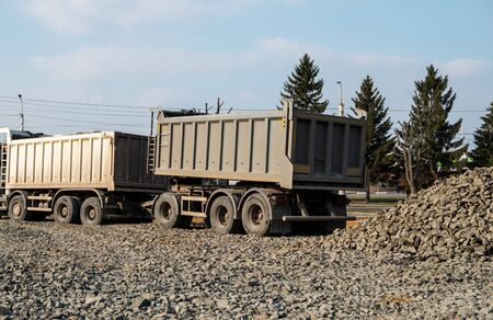 A dump truck is dumping gravel on a construction site. Dump truck dumps its load of gravel on a new road construction project. Road building. Preparing of the fundament for a asphalting