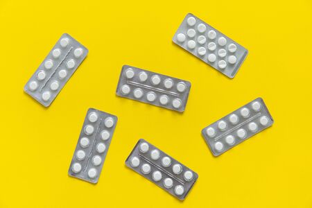 Top view on the pills in the package. White pills on yellow background. Medicine, medication, painkillers, tablet, medicaments, drugs, antibiotic, vitamin, treatment, capsule, dose. Pharmacy theme.
