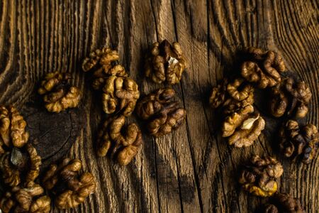 Walnut scattered on the wooden vintage table. Copy space. Walnuts is a healthy vegetarian protein nutritious food. Almonds on rustic old wood