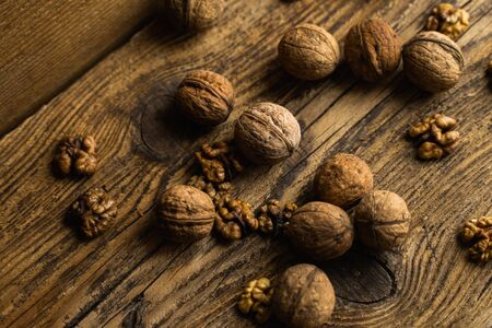 Walnut scattered on the wooden vintage table. Walnuts is a healthy vegetarian protein nutritious food. Walnut on rustic old wood