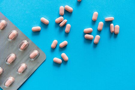 Top view on the pills removed from the pack. Pink pills on blue background. Medicine, medication, painkillers, tablet, medicaments, drugs, antibiotic, vitamin, treatment, capsule, dose. Pharmacy theme. Stok Fotoğraf