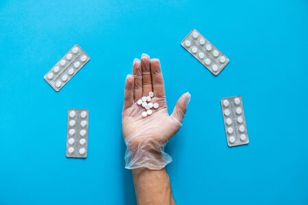 Hand of the doctor holding a white pills on blue background and packs of the pills lying near. Medicine, medication, painkillers, tablet, medicaments, drugs, antibiotic, vitamin. Pharmacy theme. Stok Fotoğraf