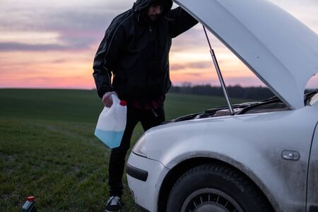 Man standing near car with open hood and holding a bottle with blue fluid on sunset. Car breakdown. Confused man stands with open hood with selective soft focus. Stock Photo