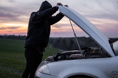 Man standing near car with open hood on sunset. Car breakdown. Confused man stands with open hood with selective soft focus.
