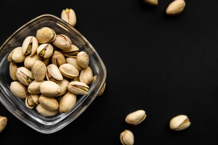 Pistachios in a small plate with scattered nuts of almonds around a plate on a black surface. Pistachio is a healthy vegetarian protein nutritious food. Natural nuts snacks. Standard-Bild