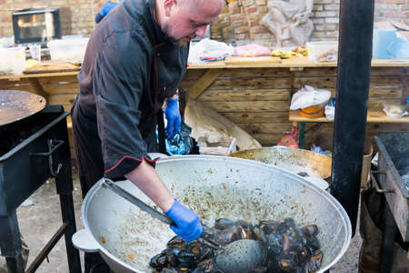 UKRAINE, LUTSK - June 5, 2019: Man is cooking a fresh mussels in shells in large metallic grill pan on a food fest.