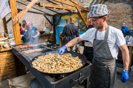 UKRAINE, LUTSK - June 5, 2019: Man is cooking a fresh mussels in shells in large metallic grill pan on a food fest.