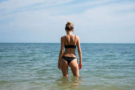 Young woman standing on a beach and enjoying the sun. Young woman in bikini looking at sea water on the beach of tropical resort. Rear view. Vacation and travel concept. 免版税图像 - 150641679