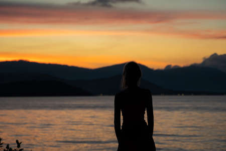 Silhouette of a woman watches sunset over a sea or ocean on a tropical island Foto de archivo
