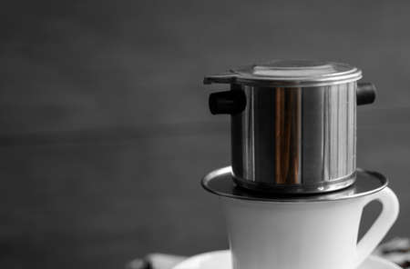 White cup of coffee with a metal filter on a top and scattered beans on a wooden table. Traditional vietnamese coffee.