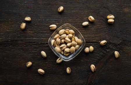 Pistachios in a small plate with scattered nuts of almonds around a plate on a vintage wooden table as a background. Pistachio is a healthy vegetarian protein nutritious food. Natural nuts snacks.