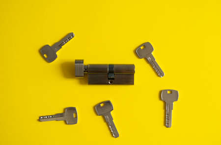 A door lock cylinder core with keys on the yellow background. The cylinder of the lock with keys. Installing a new lock on the door. Spare parts for the door. Stock fotó